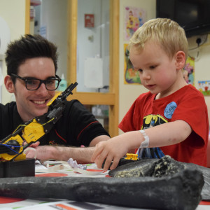 An image of a young Edinburgh Hospital patient with carer looking at an exhibit from Dynamic Earth
