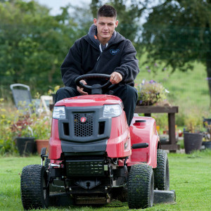 An image of a young boy driving a red lawnmower over grass.