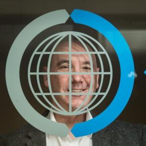 Ricky Nicol Commsworld looking through glass window and logo