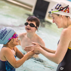 Scottish PR photograph of triple Olympian Hannah Miley teaching children to swim