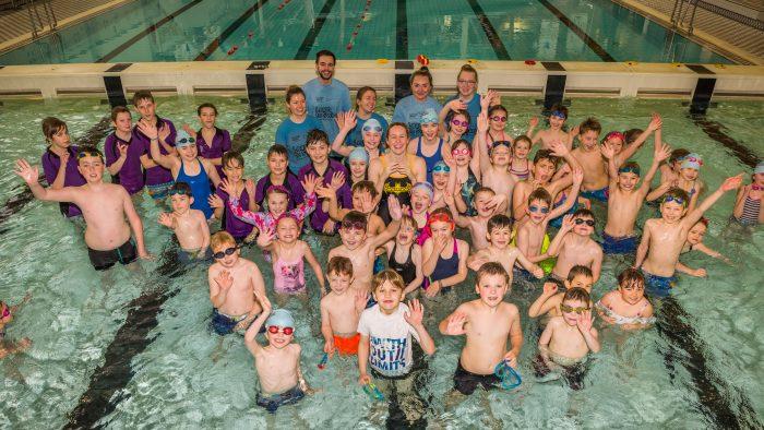 Kids splash around with Triple Olympian in PR photography