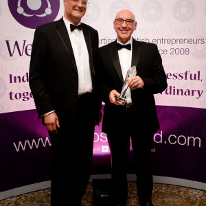 Tech PR photography shows Paul Atkinson of Par Equity and Taranta Group and Chairman of WeDO presenting lifetime achievement award to Ricky Nicol, CEO of Commsworld