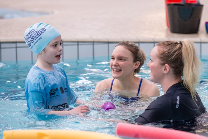 A public sector PR photo of Learn to Swim ambassador Toni Shaw with children on the programme.