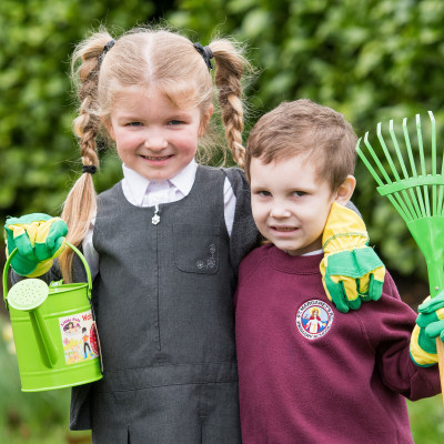 A picture of a young girl in gardening gloves holding a watering can with her arm around a young boy holding a rake. Both children are in school uniform for Photography PR