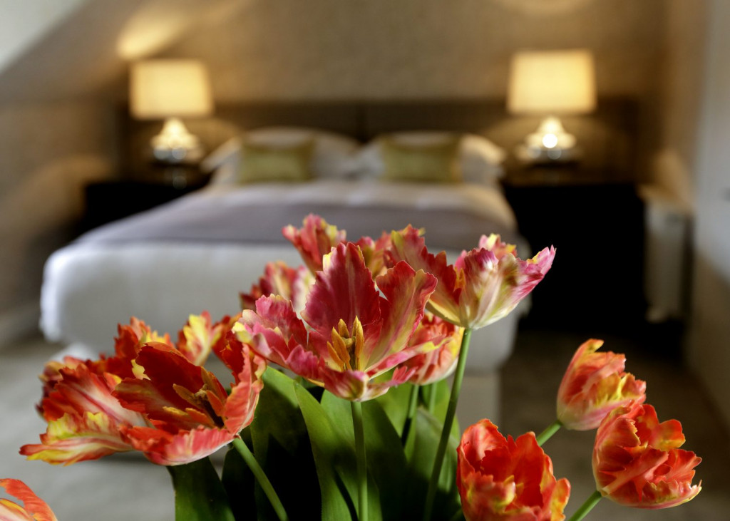Hotel PR photograph of red and yellow tulips inside a Nira Caledonia room