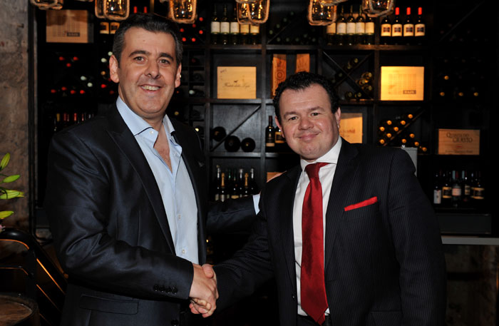 Attendees at the launch of wine bar, Divino Enoteca are shown shaking hands in a PR photgraph